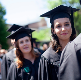 two women in graduation caps and gowns in a line of people